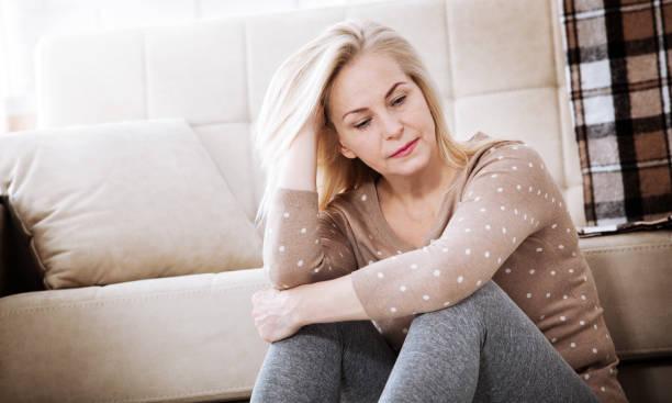 Médio com idade mulher descalça, sentado no chão abraçando os joelhos dela, perto de sofá em casa, a cabeça para baixo, entediada, com problemas com a violência doméstica. - foto de acervo
