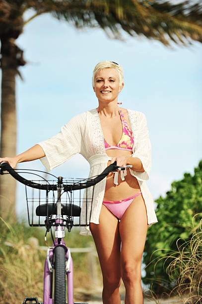 middle aged bikini model with bike at beach - older women bikini stock pictures, royalty-free photos & images