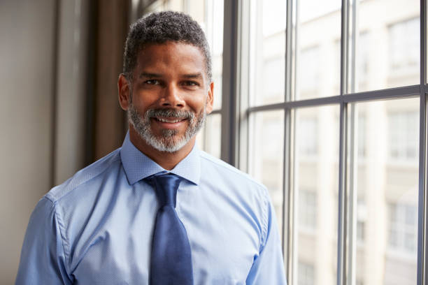 middle aged black businessman smiling to camera - professional man stock pictures, royalty-free photos & images