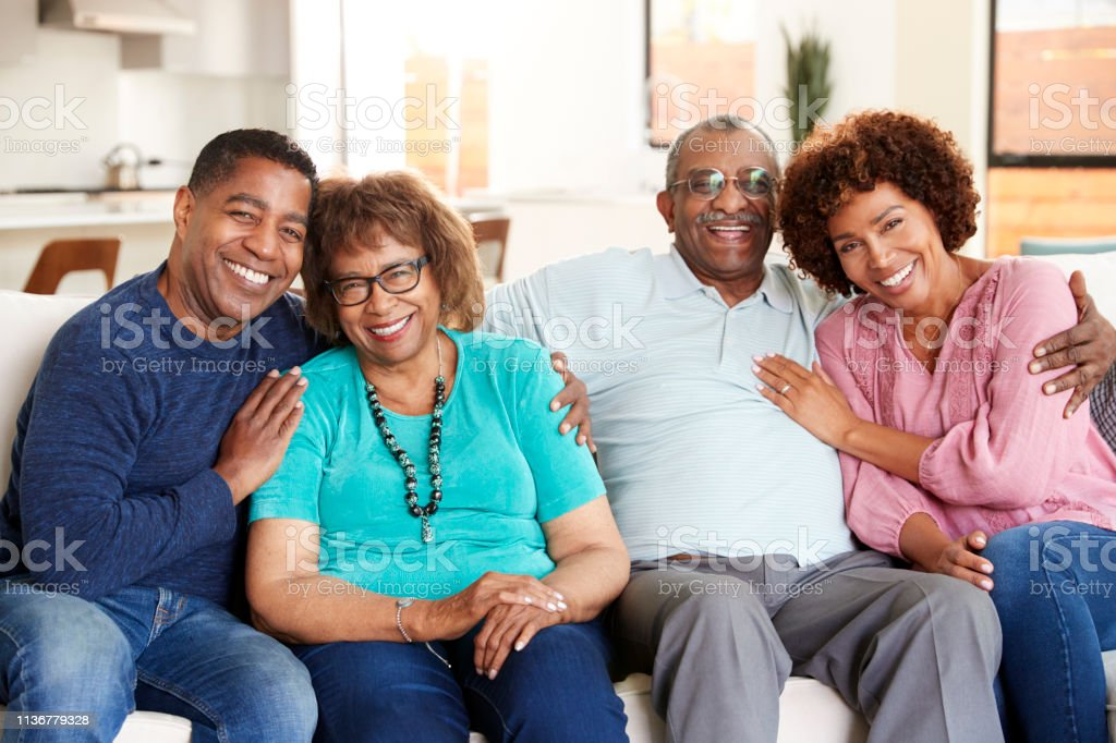 Middle aged black couple and parents sitting at home, smiling to...