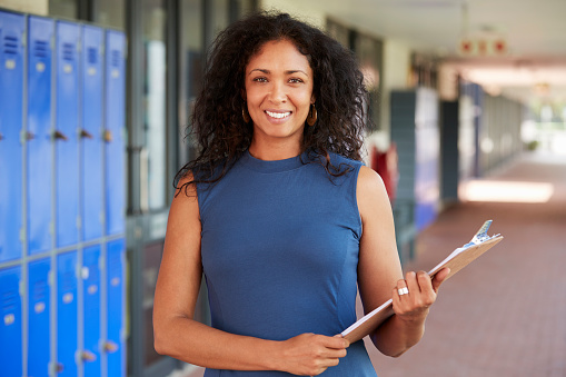 istock Middle aged black female teacher smiling in school corridor 826213524