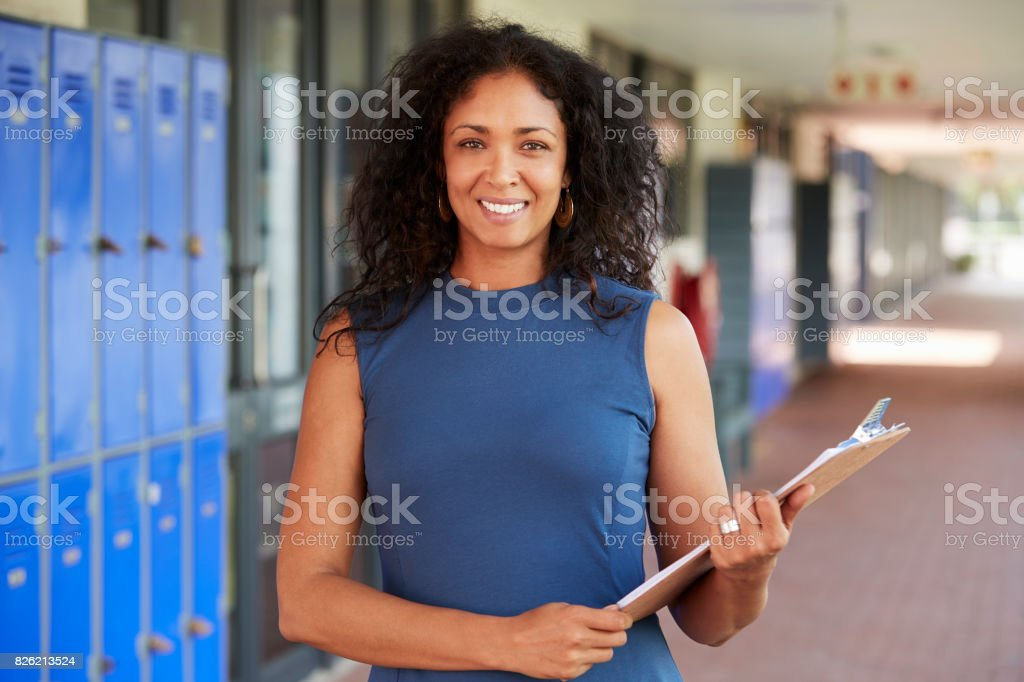 Middle aged black female teacher smiling in school corridor stock photo