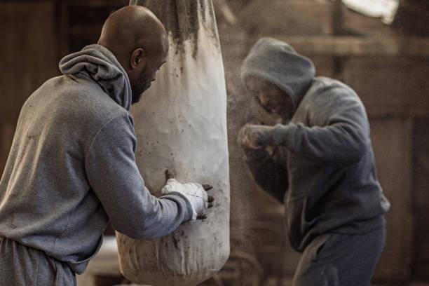 Middle aged black fighter working out with young black coach stock photo