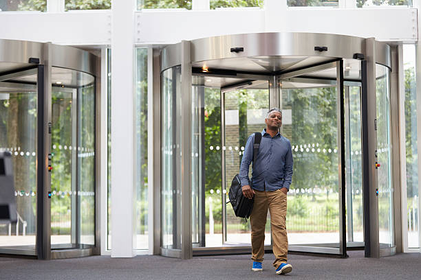 middle aged black man entering the foyer of modern building - terugkomen stockfoto's en -beelden