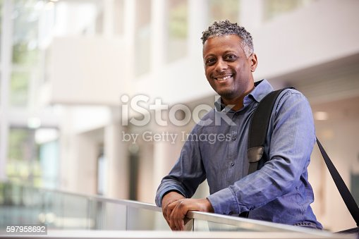 Middle aged black man  smiling in modern building lobby