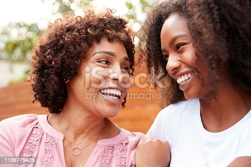 Middle aged black mum and teen daughter smiling at each other