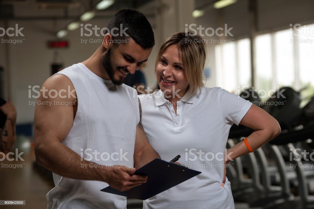 Young personal trainer standing together with female client,...