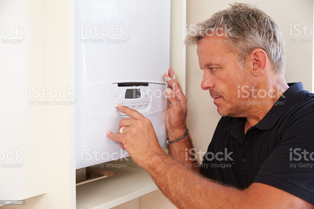 Middle aged boiler technician servicing a domestic boiler stock photo