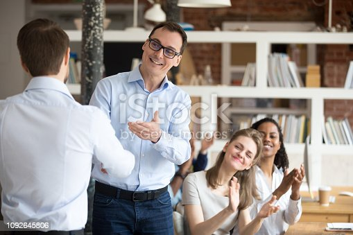 924520144 istock photo Middle aged boss, mentor congratulating employee, shaking hand 1092645806