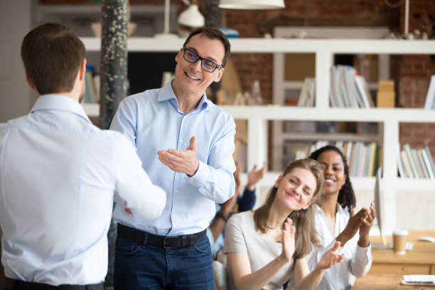 Middle aged boss, mentor congratulating employee, shaking hand Middle aged happy smiling boss, mentor congratulating employee, praise for good work, new project, idea for startup, shaking hand, welcoming new member of business team, colleagues applauding dignity stock pictures, royalty-free photos & images