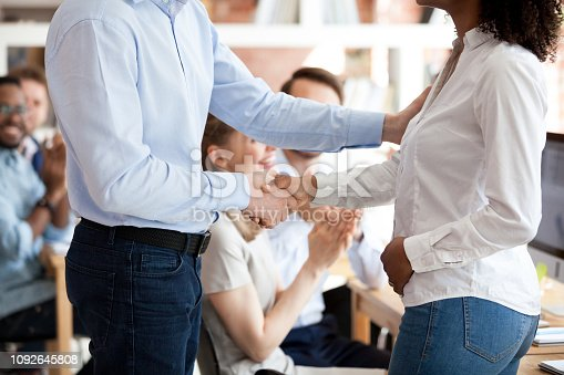istock Middle aged boss shaking hand African American employee 1092645808