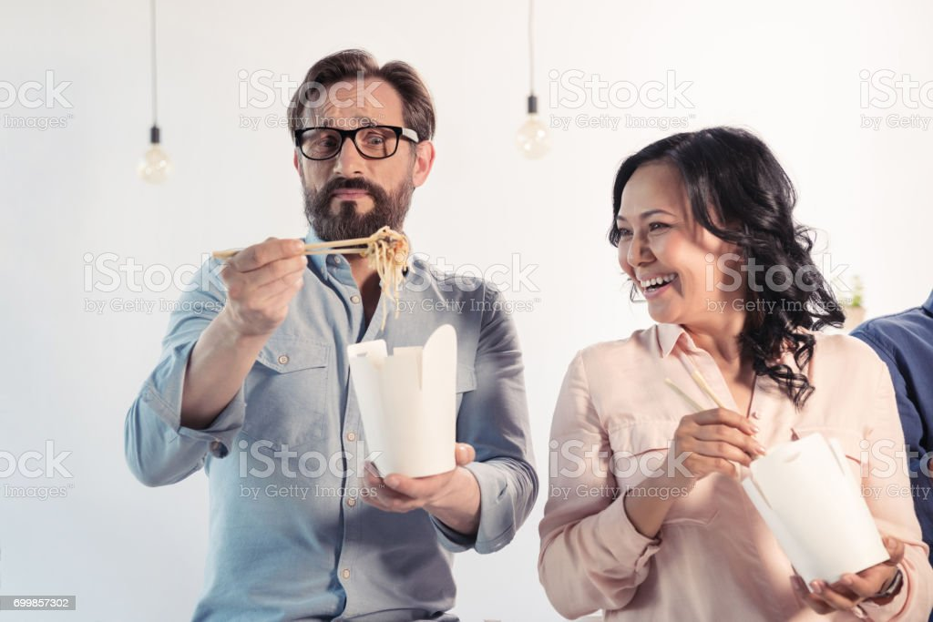 Middle aged business colleagues eating asian food with chopsticks in office stock photo