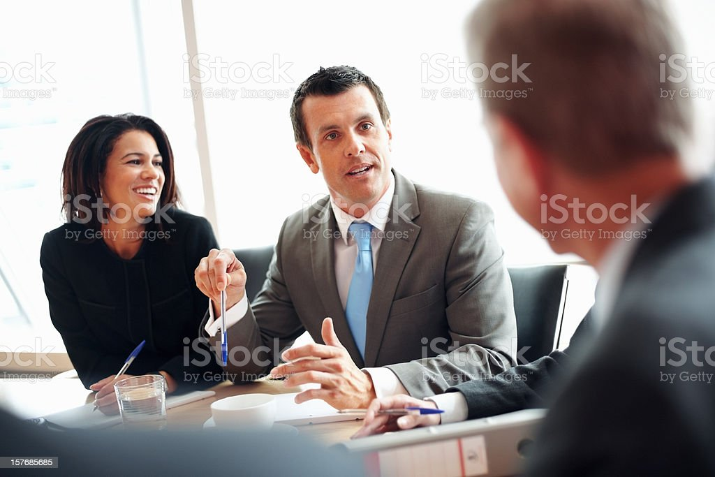 Middle aged business man discussing something with colleagues royalty-free stock photo