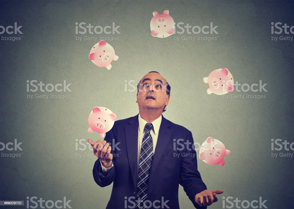 Middle aged business man juggling money piggy bank stock photo