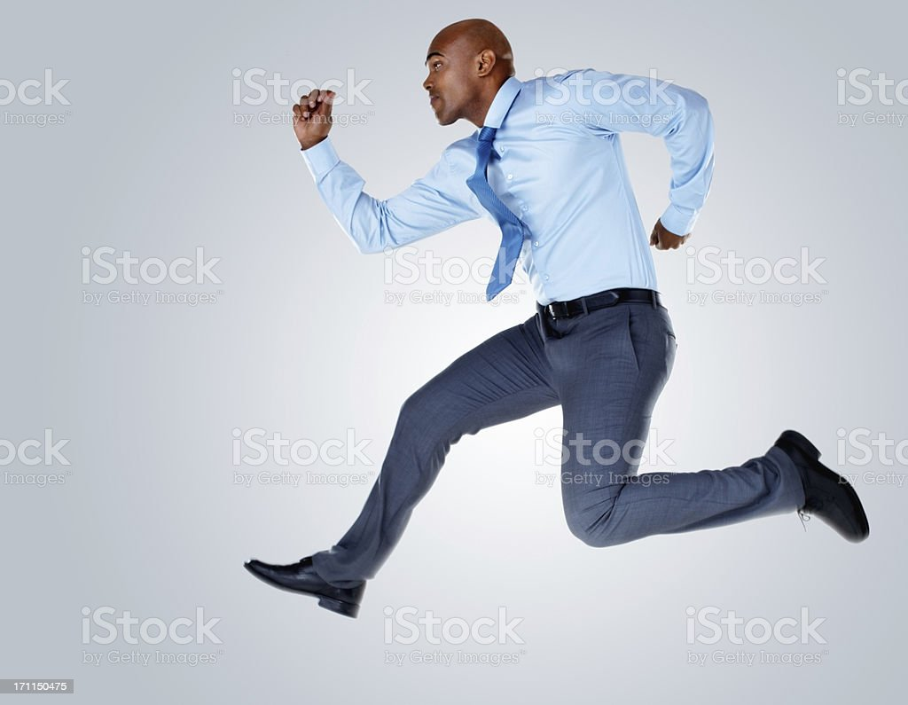 Middle aged business man running against colored background royalty-free stock photo