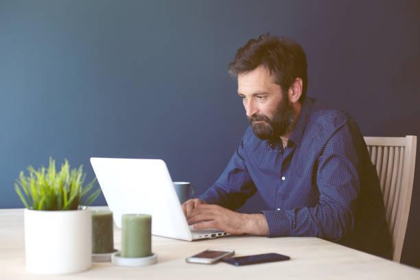 그의 홈 오피스에서 일 하는 중 년 비즈니스 남자 - 한 명의 성년 남자만 뉴스 사진 이미지