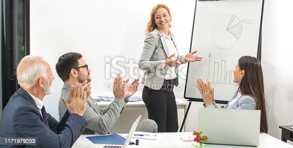 istock Middle aged business woman giving presentation on flipchart to her colleagues while they clapping hands and celebrating successful business seminar 1171979253