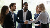 50s business lady shake hands greeting caucasian millennial businessman surrounded by multi ethnic businesspeople in formal suits. Sign contract express trust, partnership, start group meeting concept