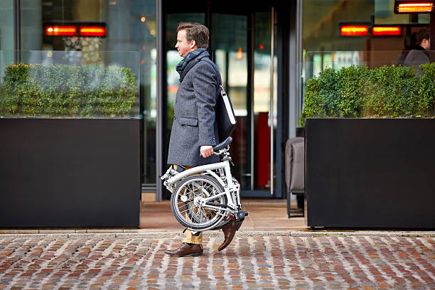 Middle aged businessman carrying his folding bicycle Middle aged businessman carrying his folding bicycle on sidewalk by the street foldable stock pictures, royalty-free photos & images
