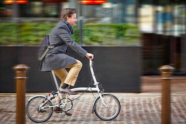Middle aged businessman going to office by cycle Middle aged businessman going to office by brompton cycle - Motion blurred foldable stock pictures, royalty-free photos & images