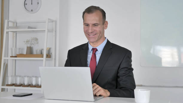 middle aged businessman talking during online video chat - video call стоковые фото и изображения