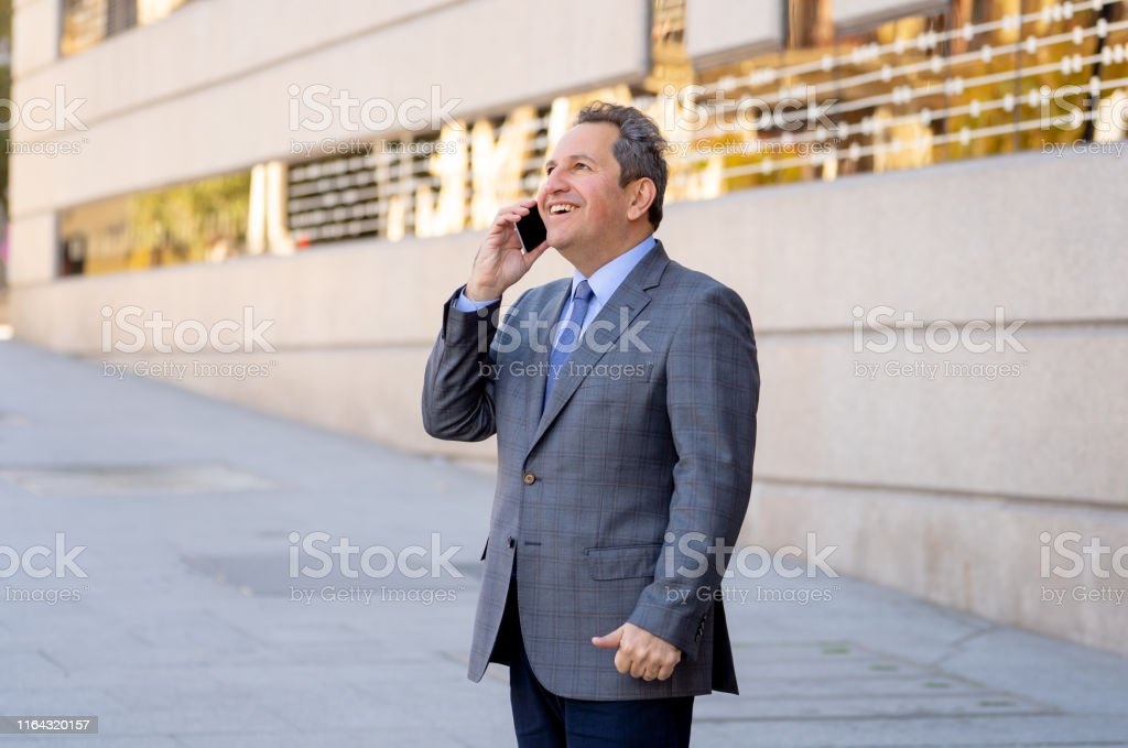 Middle aged businessman talking on smart mobile phone in urban city...