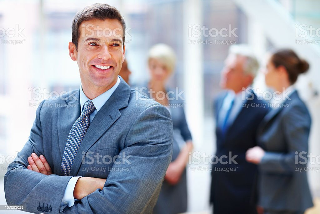 Middle aged businessman with hands folded and team in background royalty-free stock photo