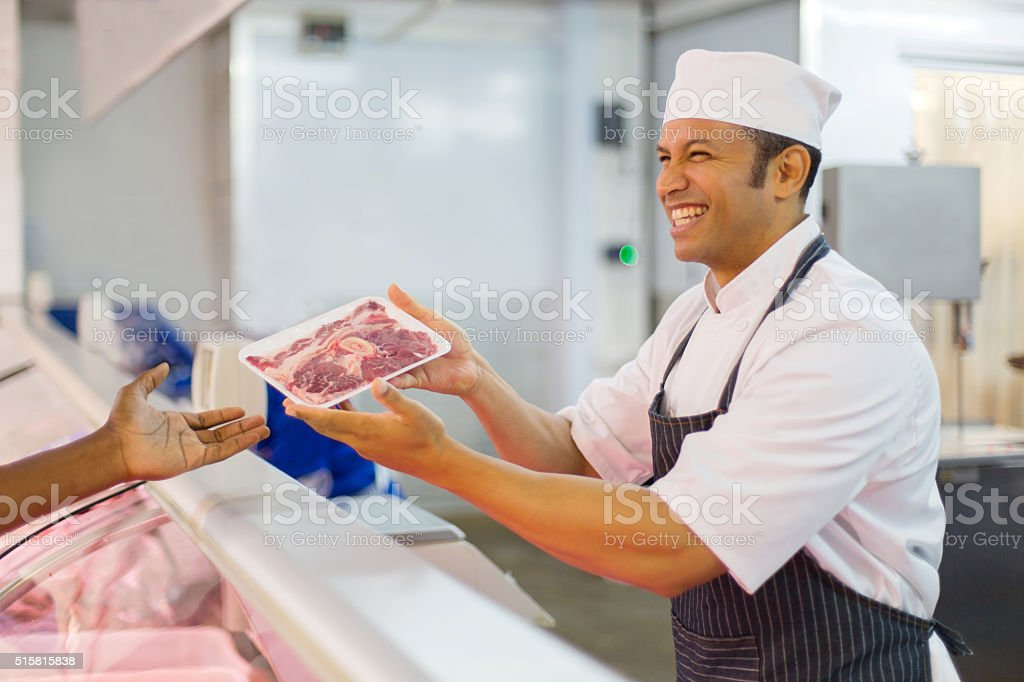 middle aged butcher serving customer stock photo