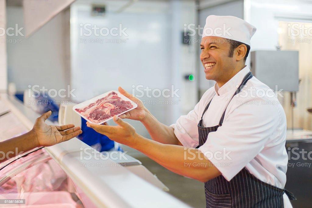 Milieu âgé de boucher pour le client - Photo