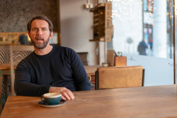 Middle aged caucasian male sitting at the table in coffee shop expressing disbelief and dislike stock photo