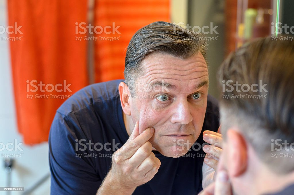 Middle aged caucasian man stands at mirror stock photo