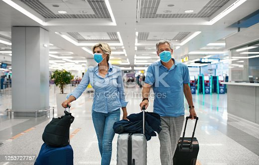 Closeup front view of a mid 50's couple waiting for a flight after coronavirus travel ban has been lifted. Both wearing face mask while walking through almost empty airport.