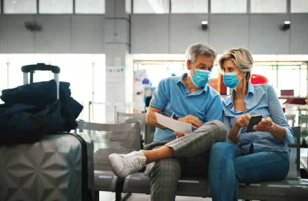 Middle aged couple at an airport during coronavirus pandemic. stock photo