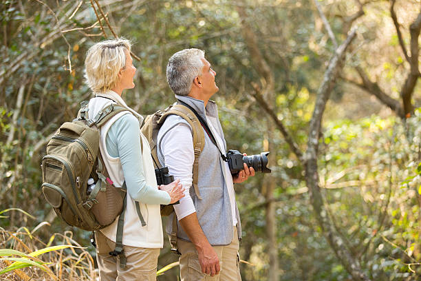 middle aged couple bird watching in forest stock photo