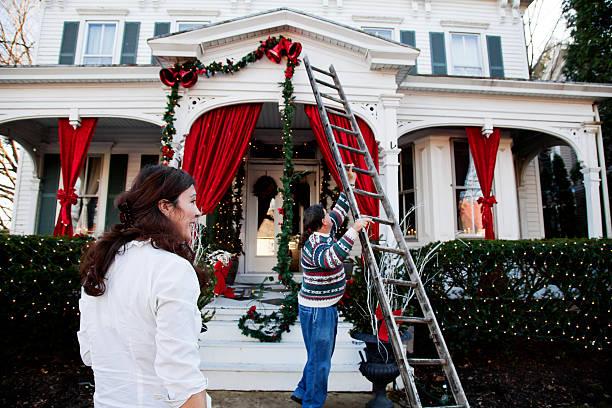 mittleren alter paar dekorieren für die feiertage - weihnachtlich dekorieren stock-fotos und bilder