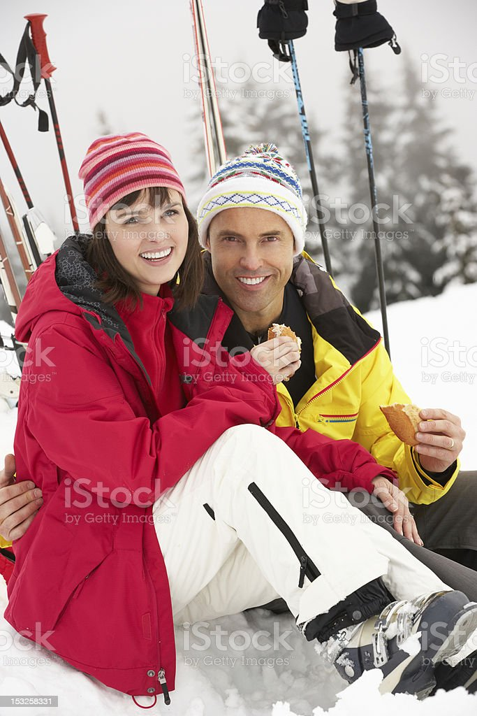 Middle Aged Couple Eating Sandwich On Ski Holiday In Mountains royalty-free stock photo