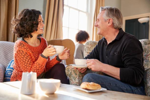 Middle Aged Couple Sitting Around Table In Coffee Shop Middle Aged Couple Sitting Around Table In Coffee Shop tea room stock pictures, royalty-free photos & images