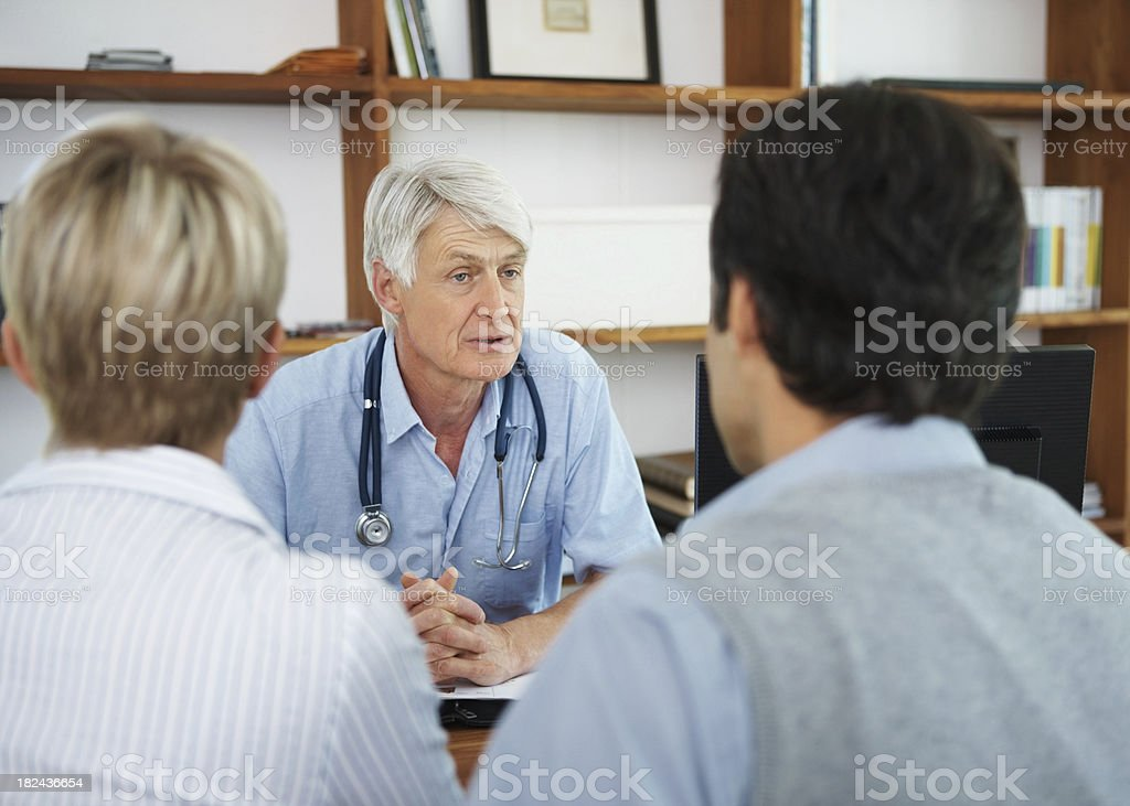 Middle aged couple visiting a doctor for checkup royalty-free stock photo