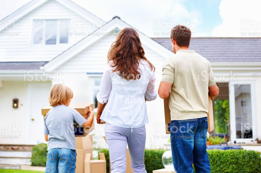 Middle aged couple with their son moving to new house stock photo