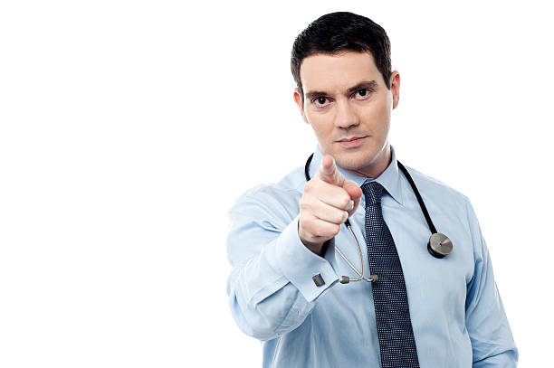 Middle aged doctor pointing at camera stock photo