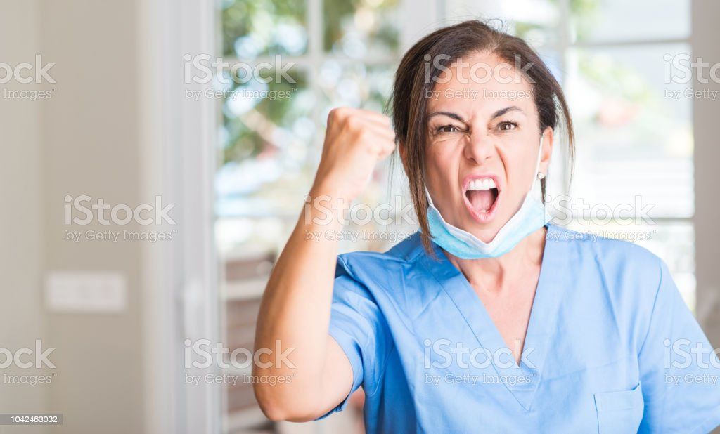 Middle aged doctor woman annoyed and frustrated shouting with anger, crazy and yelling with raised hand, anger concept stock photo