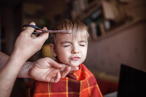 père d'âge moyen coupant des cheveux à son petit fils par lui-même à la maison, la vie pendant le verrouillage - couper les cheveux photos et images de collection