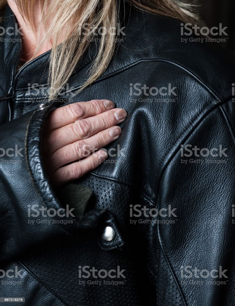 Middle aged female biker chick with blonde hair and black leather jacket. stock photo