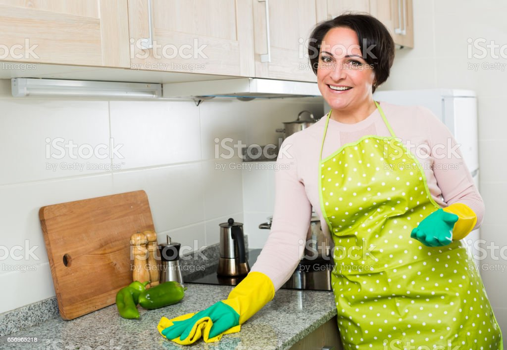 Middle aged female dusting kitchen top stock photo