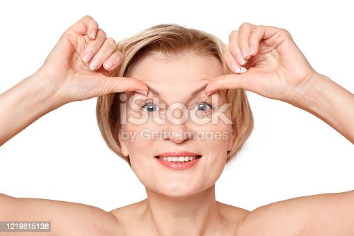 Beauty procedure concept. Portrait of smiling middle aged female lift her wrinkled skin on face up and standing isolated on white background