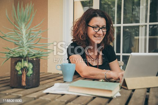 Middle aged female studying at home with books, newspaper and digital tablet pad. Woman reading a book and watching video online on new tech device. Education, modern lifestyle and leisure concept.