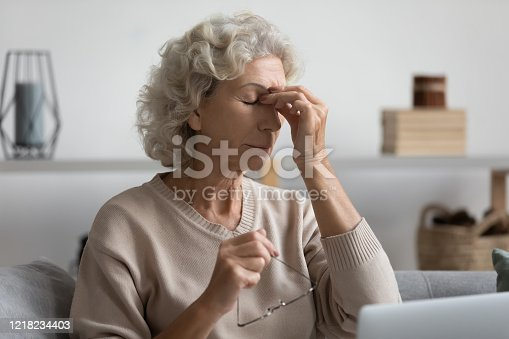 1049512672 istock photo Middle aged grandmother rubbing eye, feeling tired. 1218234403