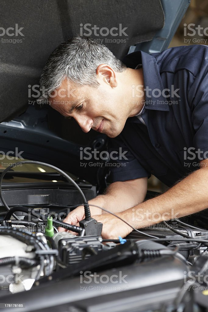 A middle aged gray haired mechanic working on engine stock photo