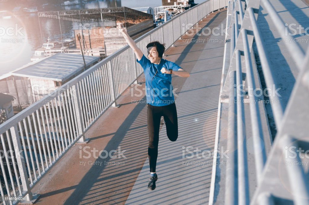 Middle aged happy woman in jogging on the city bridge.Active mature...