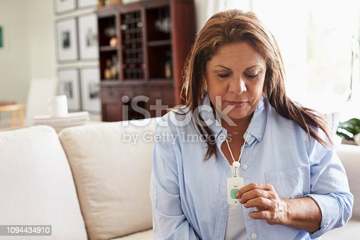 Middle aged Hispanic woman at home, pushing an assistance alarm which she is wearing around her neck